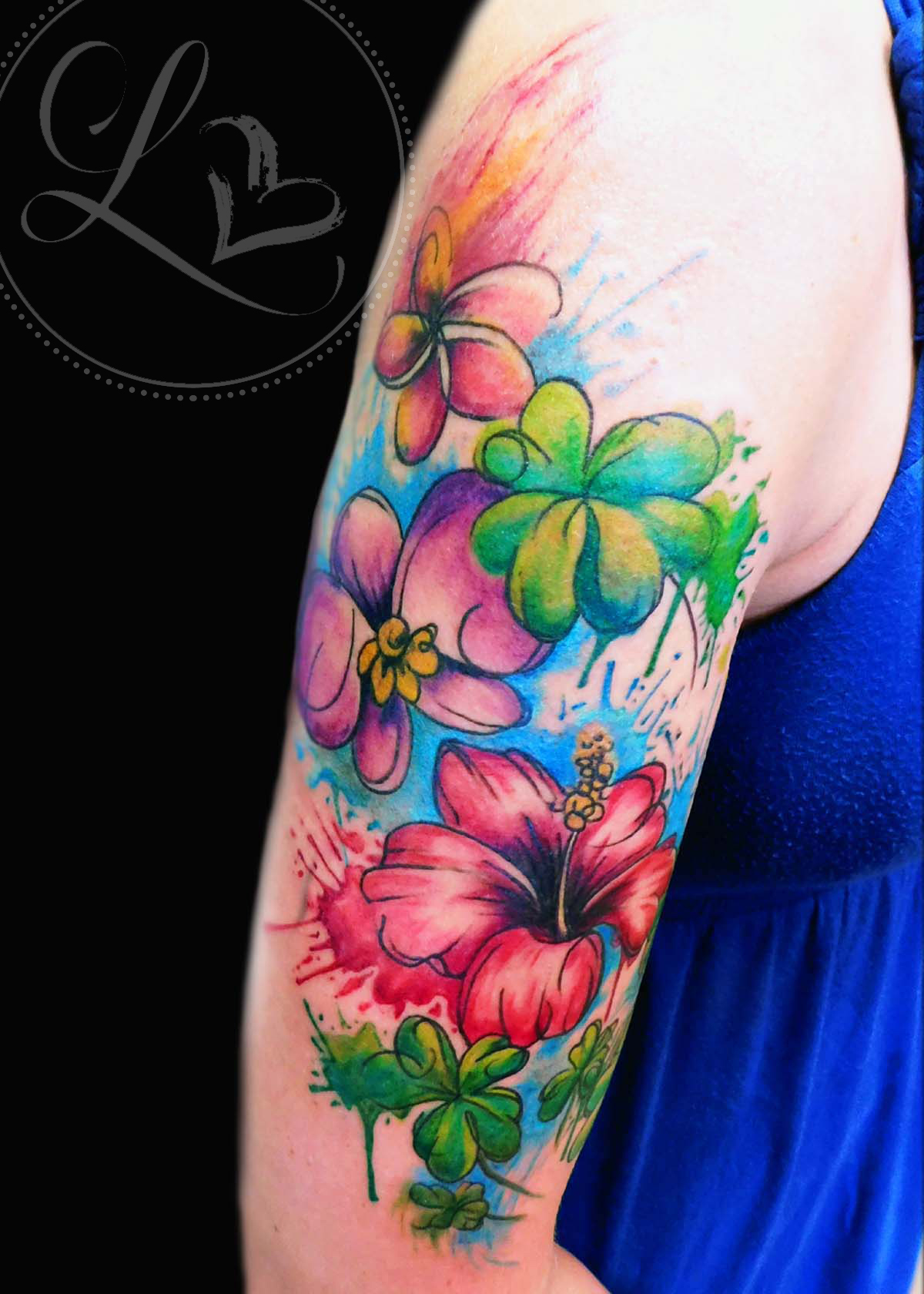 Watercolor floral half-sleeve tattoo composed of plumeria, hibiscus, orchid, and four-leaf clovers