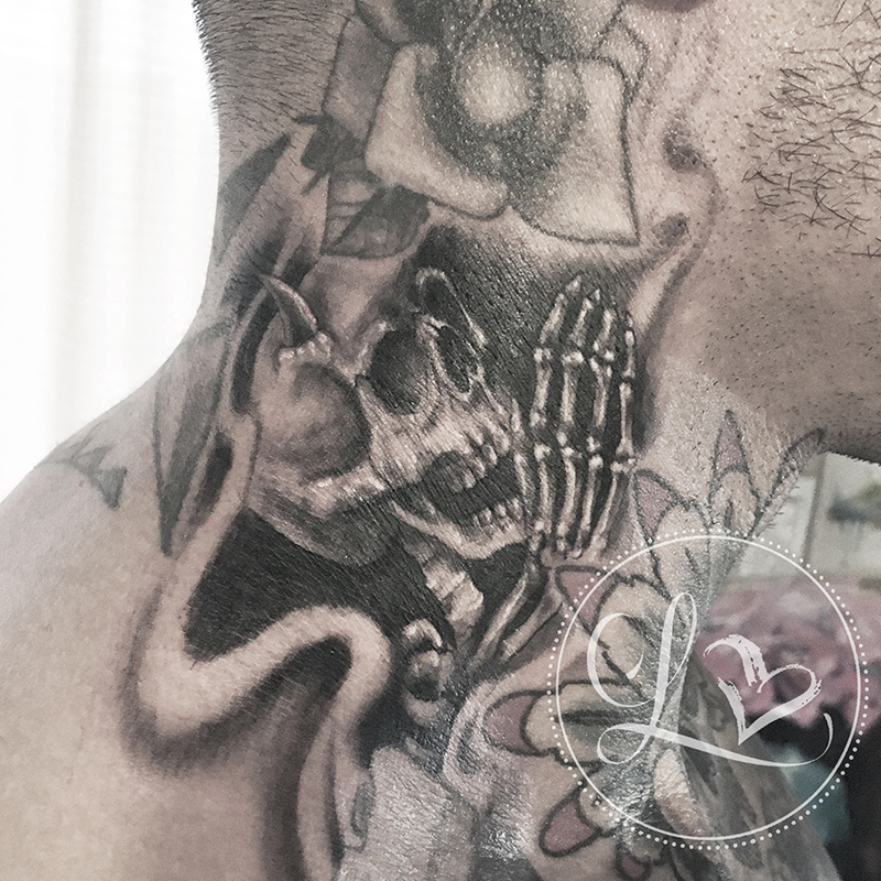 Black and grey realistic tattoo on a man's neck of a skeleton with devil horns whispering into an ear