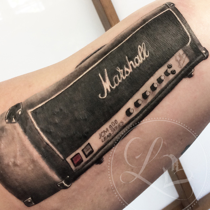 Realistic black and grey tattoo on an inner arm of a Marshall guitar amplifier