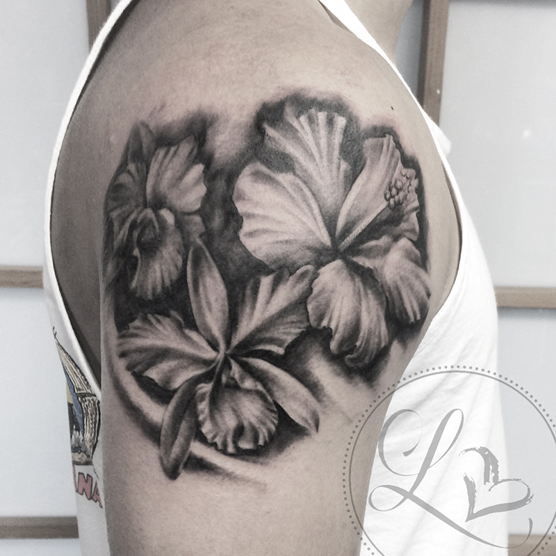 Realistic black and grey tattoo of tropical flowers hibiscus and orchid on a man's shoulder
