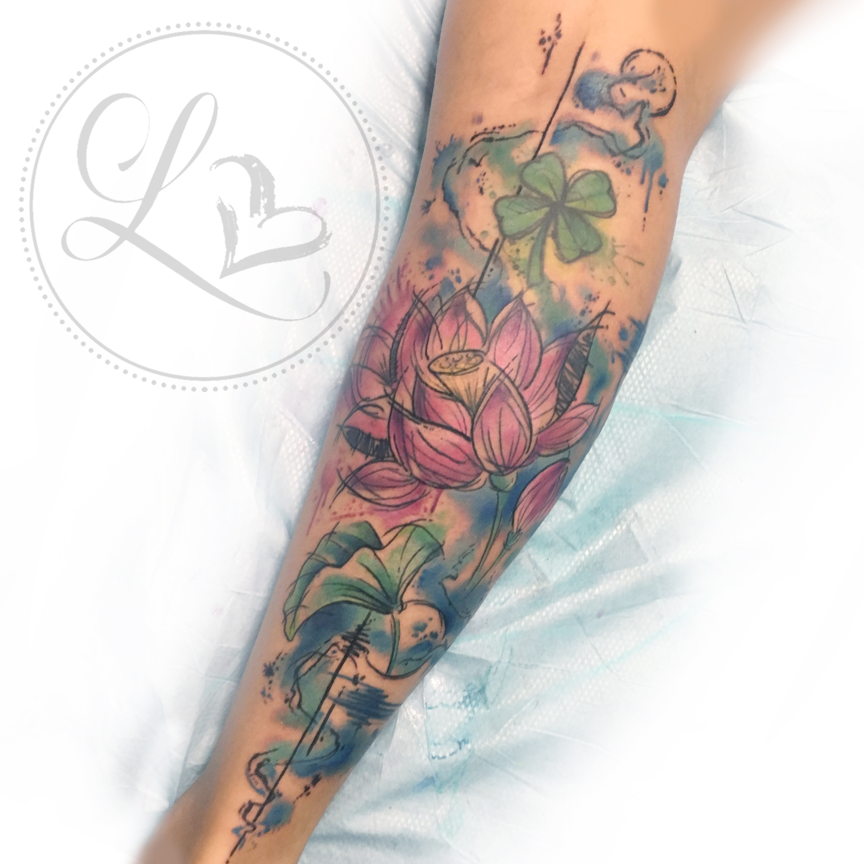 Watercolor style leg half-sleeve tattoo of lotus flowere and lily pads