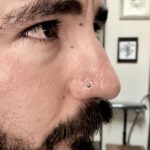 Nostril nose piercing done with a turquoise-dyed howlite cabochon nostril screw